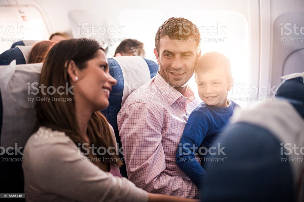 Smiling family talking while flying in the airplane. stock photo