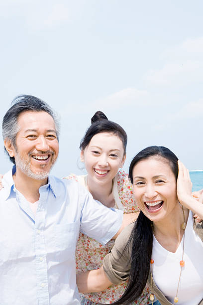 Smiling family under blue sky. stock photo