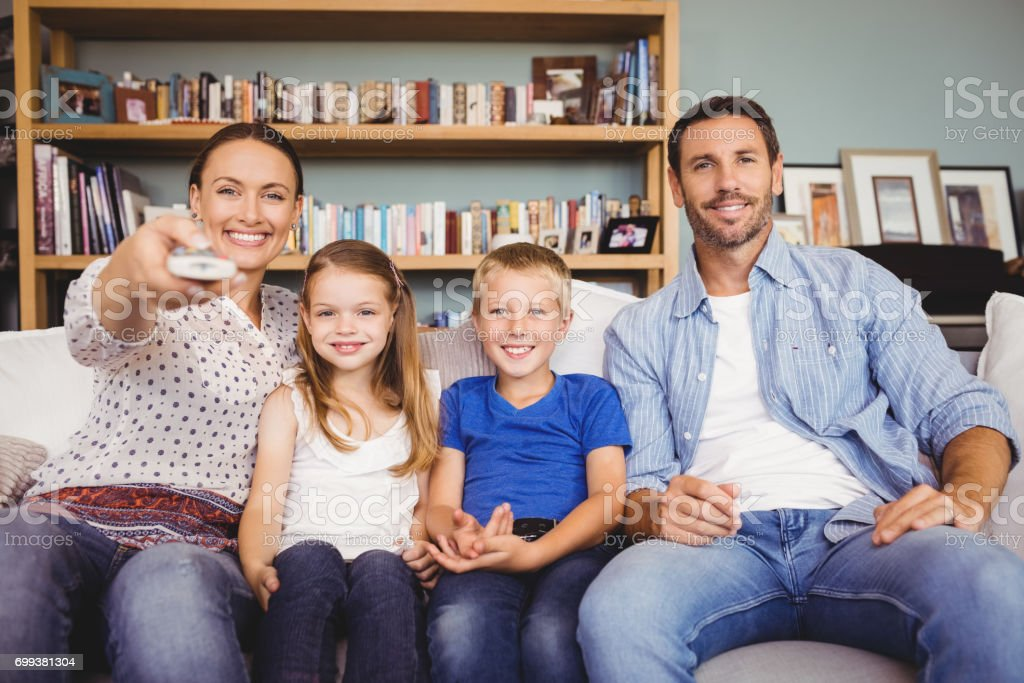 Smiling family watching television stock photo