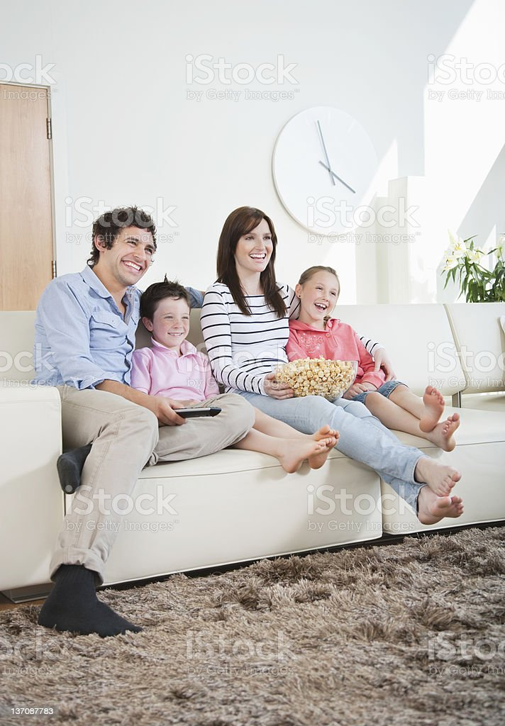 ... Smiling Family Watching TV On Sofa Stock Photo ...