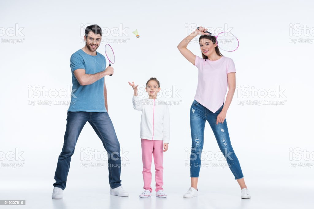 smiling family with badminton rackets and shuttlecock on white - Photo