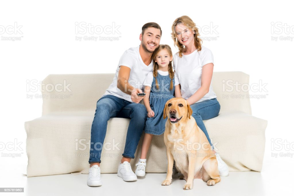 smiling family with dog watching tv on sofa, isolated on white stock photo