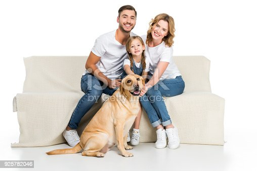 Smiling Family With Golden Retriever Dog Sitting On Sofa Isolated On