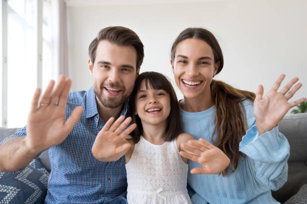Smiling family with little kid waving talking on webcam Happy parents sit on couch at home with cute little daughter wave talk on webcam, smiling young family with preschooler girl kid have skype conversation or shoot record vlog for social media together young girls on webcam stock pictures, royalty-free photos & images