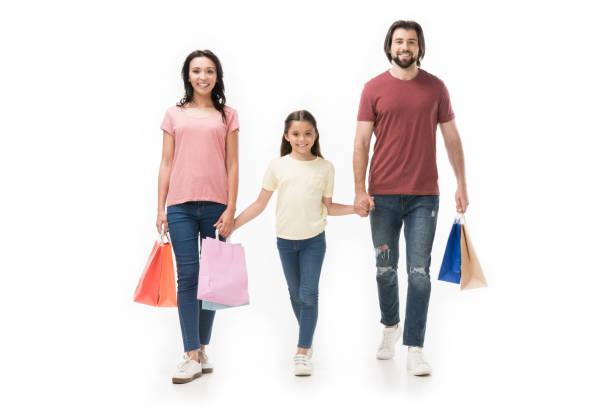 lächelnde familie mit einkaufstüten, die hand in hand, isoliert auf weiss - taschen von liebeskind stock-fotos und bilder