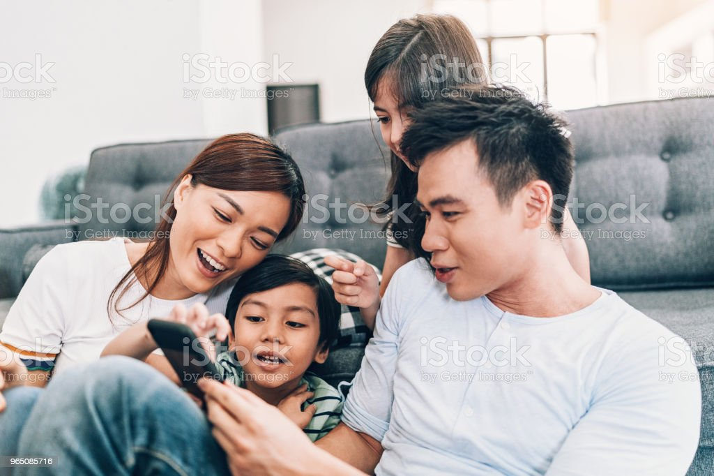 Smiling family with smart phone royalty-free stock photo