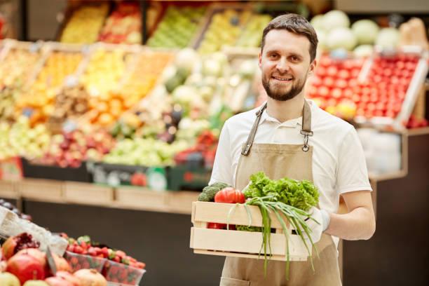 Smiling Farmer Holding Box of Vegetables at Market stock photo
