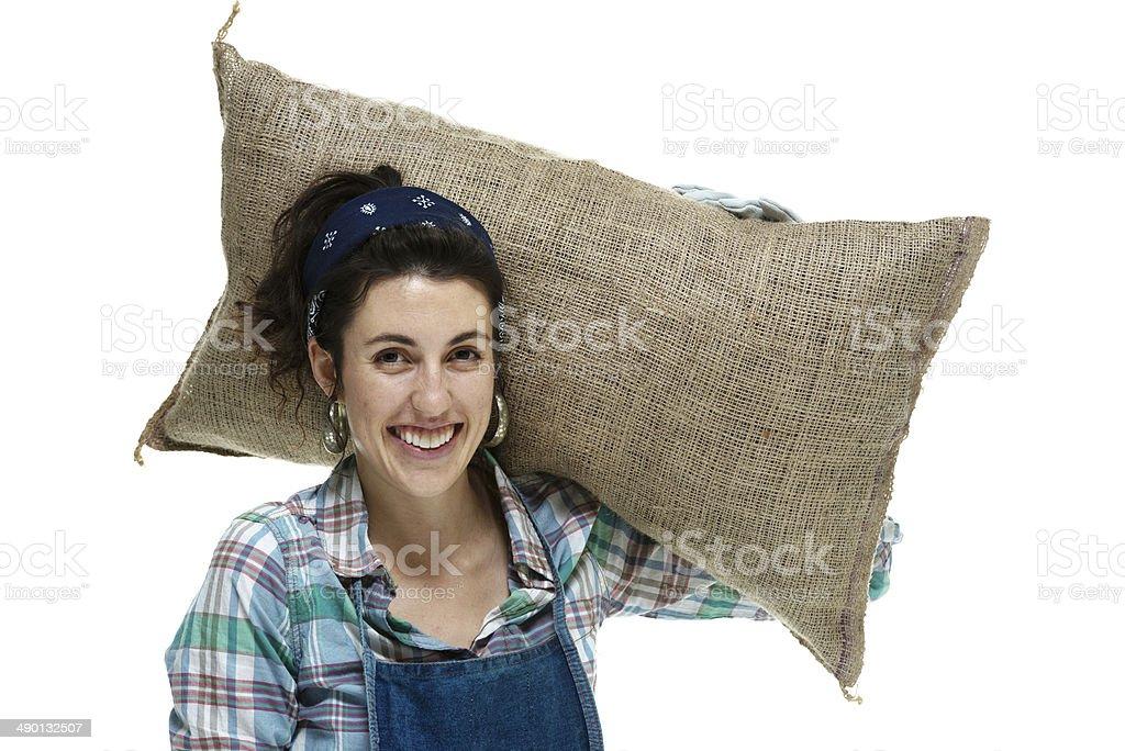 Smiling farmer holding burlap sack stock photo