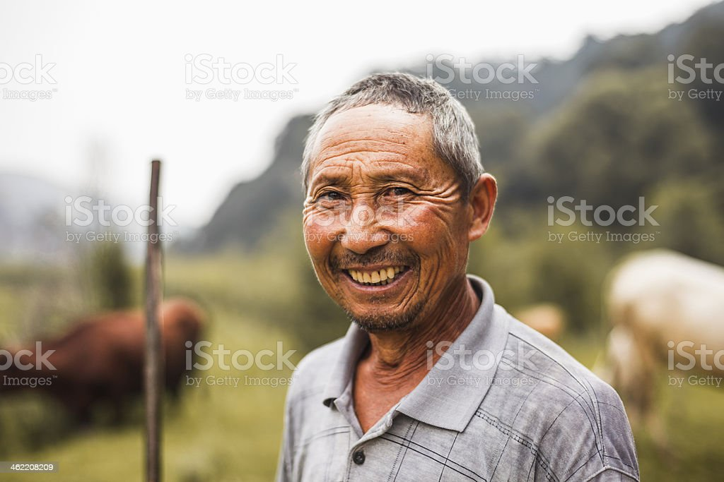Smiling farmer with livestock in background, rural China, Shanxi Province stock photo