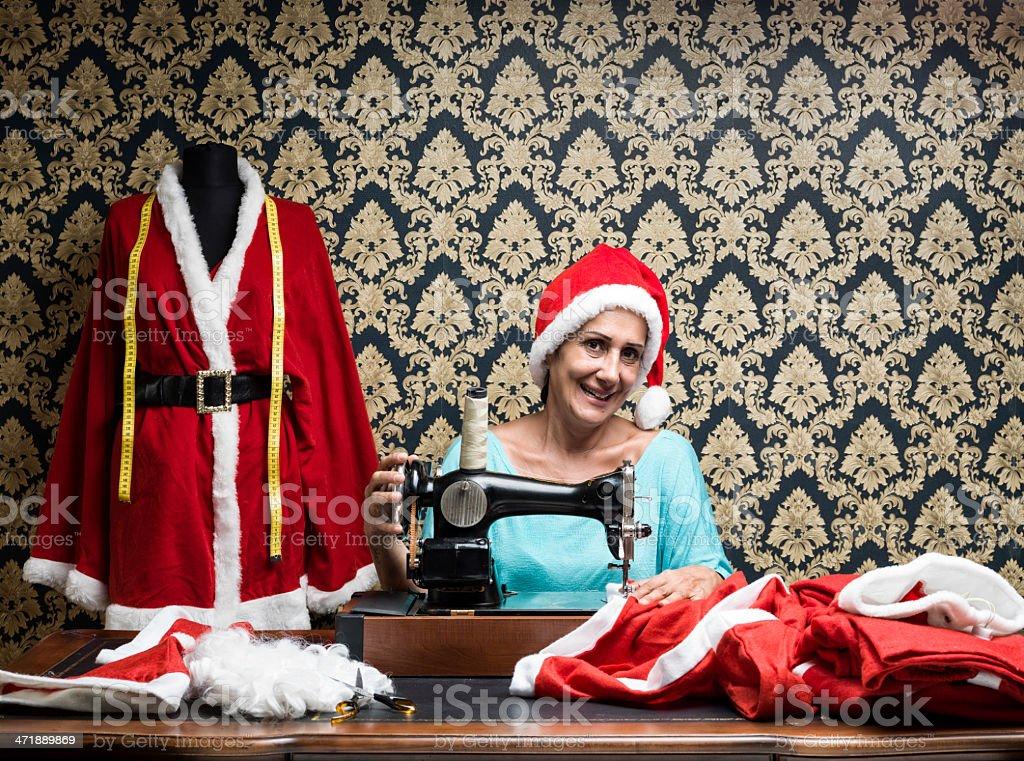 Smiling fashion designer sewing santa costume for christmas royalty-free stock photo
