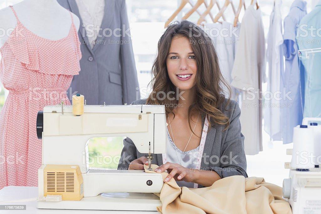 Sonriendo diseñador de moda usando máquina de coser foto de stock libre de derechos