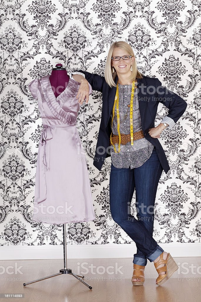 Smiling fashion designr steanding near a mannequin royalty-free stock photo