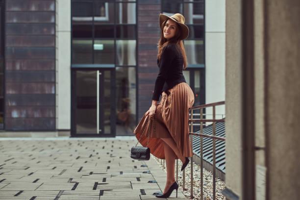 lächelnde mode elegante frau trug eine schwarze jacke, braune hut und rock mit einer handtasche clutch posiert und stützte sich auf ein stahlgeländer im zentrum europäischen stadt. - damen rock lang stock-fotos und bilder