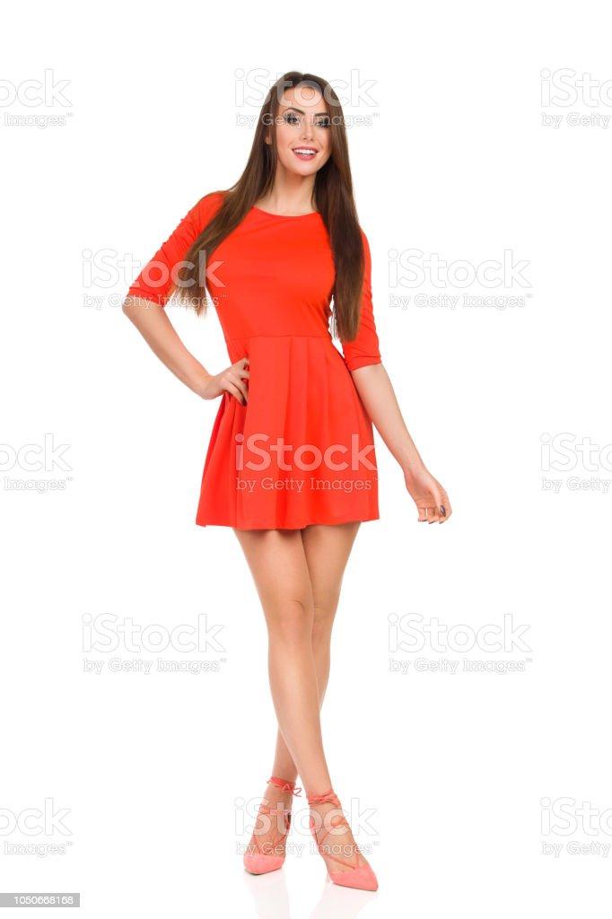 7aae336b929 Sourire de mannequin en robe Mini rouge et des talons hauts est debout avec  les jambes