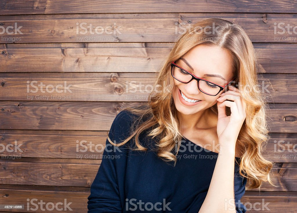 Smiling fashionable blonde laughs outdoors on wooden background stock photo