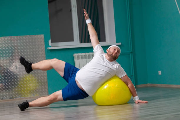 Smiling fat man is doing exercises using fitness ball. Overweight man is happy with the result of his training in group fitness classes stock photo