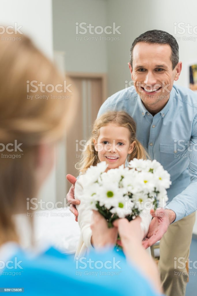 smiling father and daughter bringing flowers to sick woman stock photo