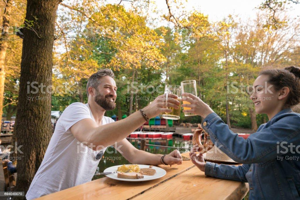 Lächelnden Vater und Tochter, die Getränke und Snacks in einem Bier-Garten auf sonnigen Tag – Foto