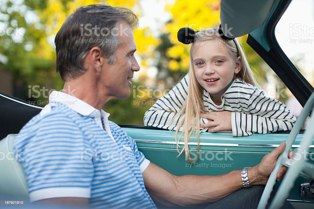 Smiling father and daughter in convertible royalty-free stock photo