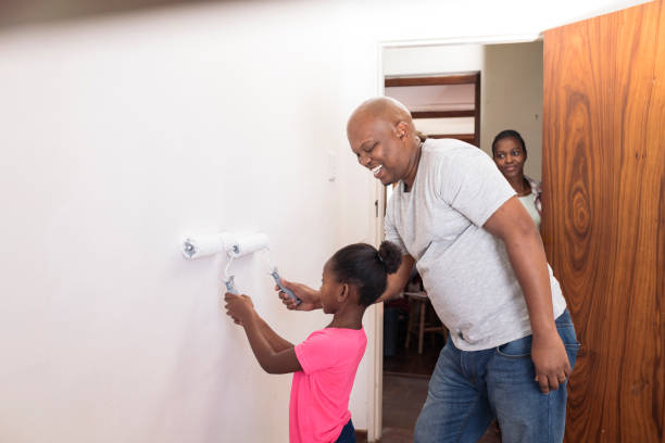 Smiling father and daughter painting together with mother looking in the background stock photo