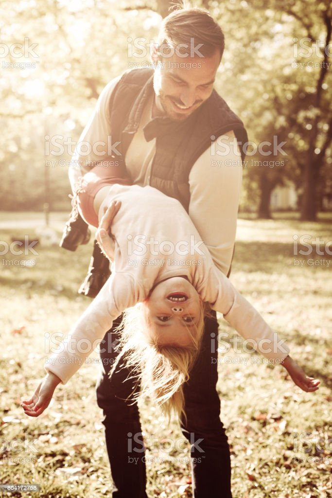 Smiling father and his daughter playing together in autumn day and enjoying in park. royalty-free stock photo