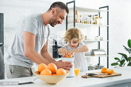 smiling father and little son making fresh orange juice by squeezer on table at kitchen