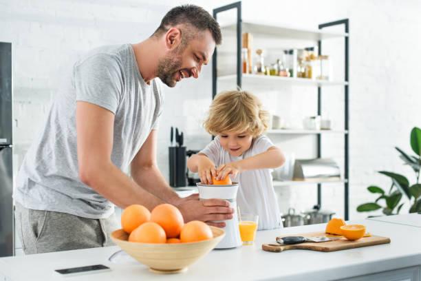 lächelnd, vater und kleinen sohn indem squeezer am tisch in der küche frisch gepresster orangensaft - innocent saft stock-fotos und bilder