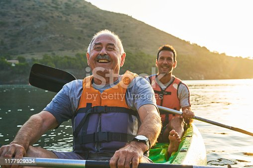 Smiling father and son kayaking on river. Family enjoying aquatic sport against mountain. They are happy during vacation.