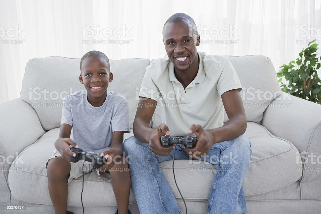 Smiling father and son playing video games together royalty-free stock photo
