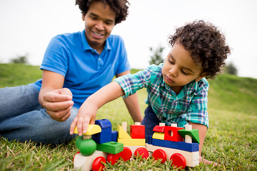 Smiling father and son playing with a toy train in a park