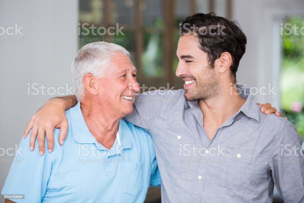 Smiling father and son with arm around stock photo