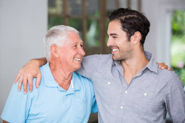 smiling father and son with arm around - son stock photos and pictures