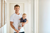 Portrait of smiling mid adult man carrying son at home. Loving father is spending leisure time with baby boy. They are wearing casuals.