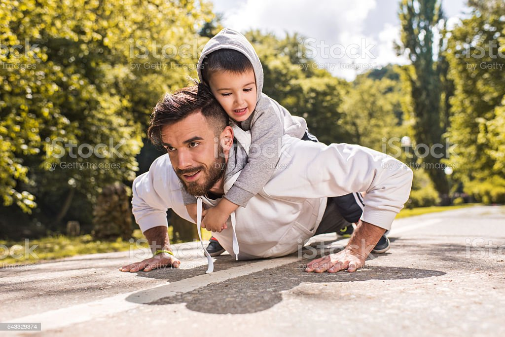 Smiling father doing push-ups with his little boy in nature. stock photo