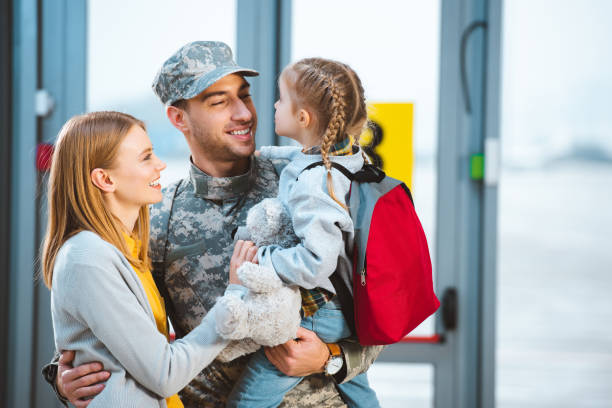 smiling father in military uniform holding in arms daughter near wife in airport - tropa imagens e fotografias de stock