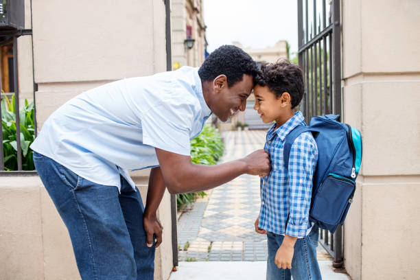 Smiling father leaving son with backpack to school stock photo