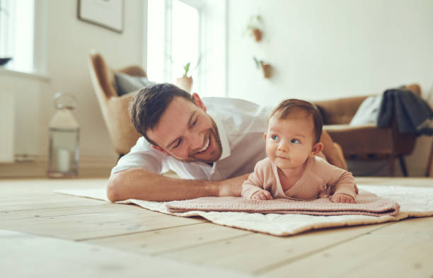Smiling father lying with his infant daughter at home stock photo