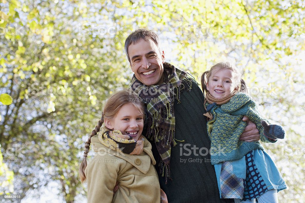 Smiling father outdoors with daughters in autumn royalty-free stock photo