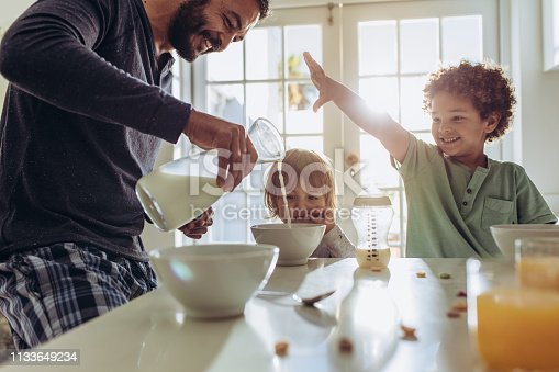 Father making breakfast for his kids at home. Man having fun preparing breakfast at home with his kids.
