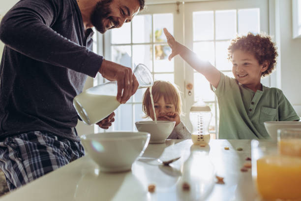 padre sonriente verter leche en tazones para el desayuno - desayuno fotografías e imágenes de stock