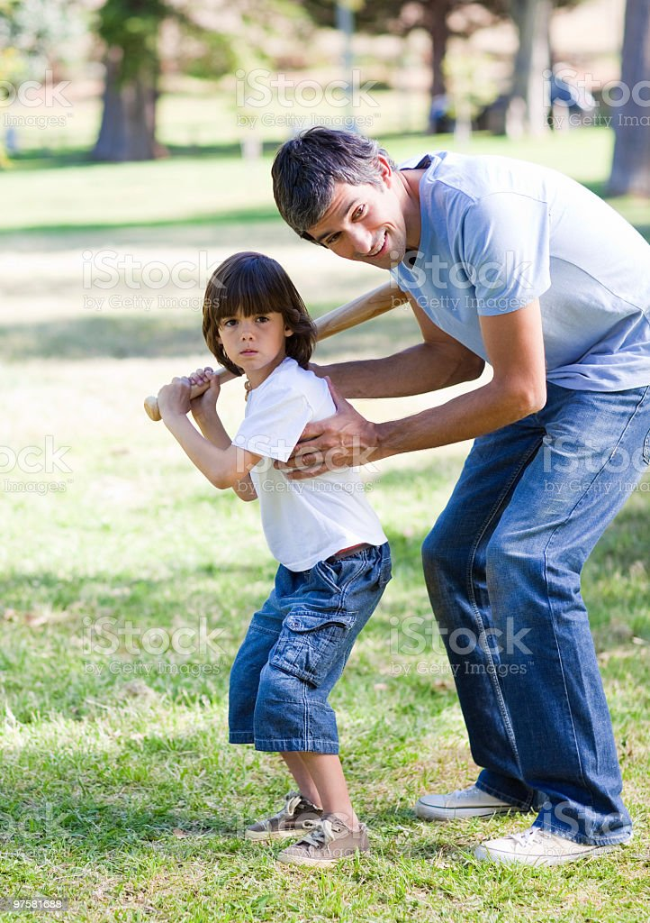 Smiling father teaching baseball to his son royalty-free stock photo