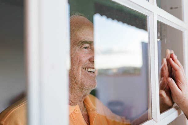glimlachende vader die het venster tijdens het bezoek van de dochter raakt - raam bezoek stockfoto's en -beelden