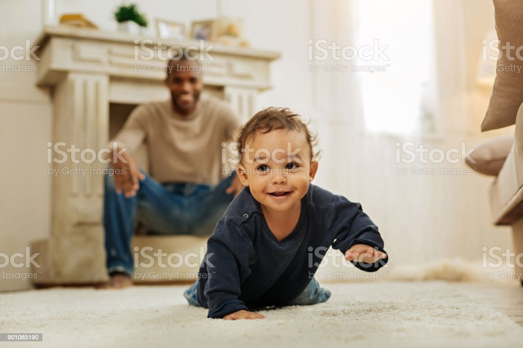 Smiling father watching his son crawling stock photo