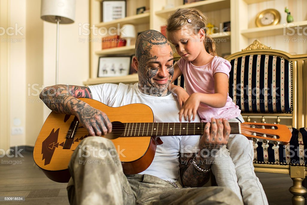 Smiling father with daughter playing acoustic guitar at home. stock photo