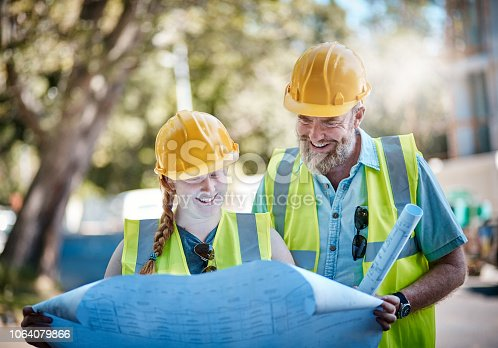 A mature man and a young woman, both construction professionals, look down at a set of building plans together, smiling.