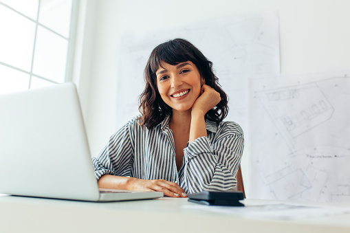 Close up of a smiling female entrepreneur. Businesswoman sitting at her desk working on laptop.