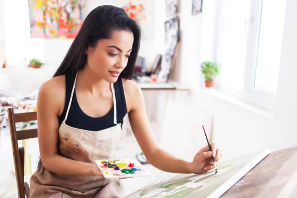 artiste féminine souriant, au studio de dessin - gaucher photos et images de collection