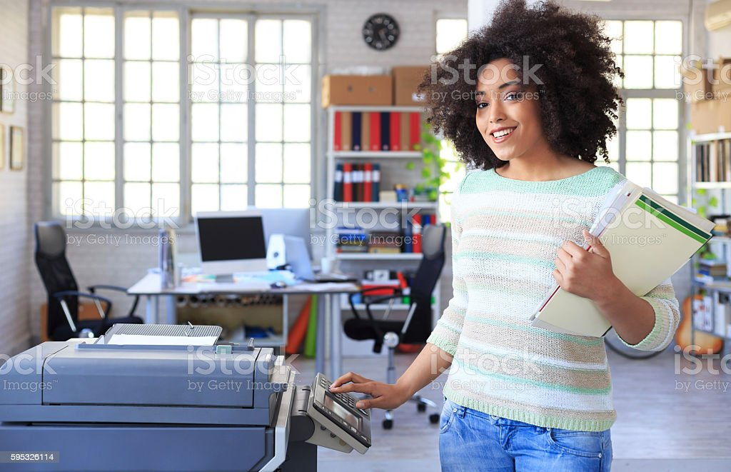 Smiling female assistant using copy machine at workplace stock photo