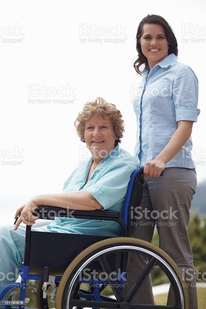 Smiling female assisting senior lady on wheelchair royalty-free stock photo