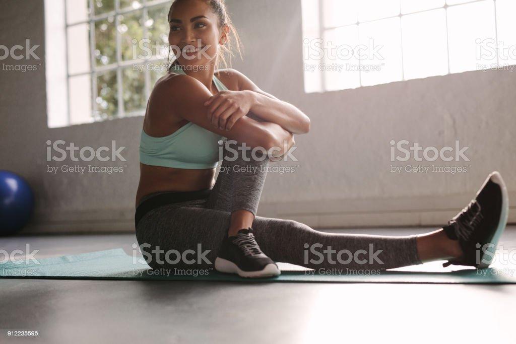 Sonriente mujer en el gimnasio tomando un descanso de entrenamiento foto de stock libre de derechos